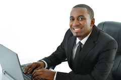 Businessman typing on laptop. Business man sitting with a laptop looking straight Stock Photos
