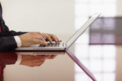Businessman typing on laptop computer. Closeup of caucasian mid adult male typing on laptop pc in meeting room. Horizontal shape, side view, copy space stock photography