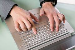 Businessman typing on a laptop computer Stock Photos