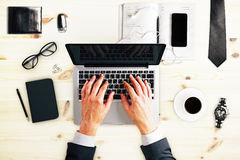 Businessman typing with laptop, eyeglasses ans other accessories Stock Photo