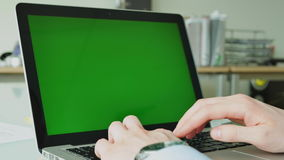 Businessman typing on the Laptop with green screen on glass table in the office. Businessman typing on the Laptop with green screen on modern glass table in the stock video footage