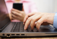 Businessman is typing on laptop keyboard with woman in blurred b Stock Photography