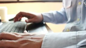 Businessman typing on a laptop keyboard in blurred focus. Businessman typing on a laptop keyboard for work in blurred focus stock footage
