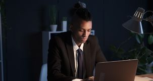 Businessman typing on laptop late in dark office. African american businessman working late night on office laptop stock footage