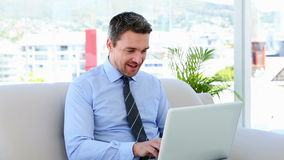 Businessman typing on laptop sitting on sofa. At home stock footage