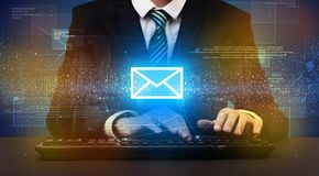 Businessman typing and mailing icon above. Businessman in suit typing with communication, mailing concept around Royalty Free Stock Photos