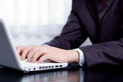 Businessman typing on a notebook. (shallow DOF, hand in focus Royalty Free Stock Image