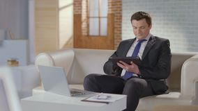 Businessman typing, scrolling pages on tablet, looking at camera. Stock footage stock video