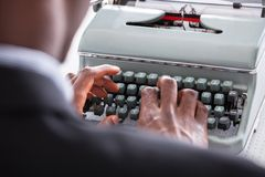Businessman Typing On Typewriter. Portrait Of Happy Business Man Typing On Typewriter Royalty Free Stock Photo