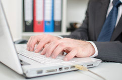 Businessman typing on a white laptop computer keyboard Royalty Free Stock Photography