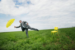 Businessman with umbrella. A businessman on one leg, appearing to be off balance or unsteady as he holds a yellow umbrella in an open field or pasture Royalty Free Stock Photography