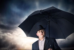 Businessman with umbrella. And storm clouds background Royalty Free Stock Photography