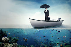 Businessman with umbrella and bag on boat Stock Image