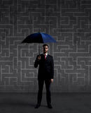 Businessman with umbrella. Black background with copyspace. Busi. Businessman with umbrella standing over labyrinth background. Business, strategy, insurance Stock Image