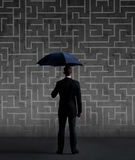 Businessman with umbrella. Black background with copyspace. Busi. Businessman with umbrella standing over labyrinth background. Business, strategy, insurance Stock Photography
