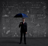 Businessman with umbrella. Black background with copyspace. Busi Stock Photo