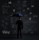 Businessman with umbrella. Black background with copyspace. Busi Stock Image