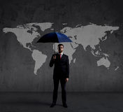 Businessman with umbrella. Black background with copyspace. Busi. Businessman with umbrella standing over world map background. Business, risk, insurance Stock Images