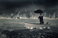 Businessman with umbrella in boat Stock Image
