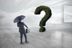 Businessman with umbrella and briefcase looking at question mark made of plants Stock Photography