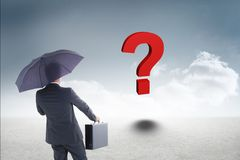 Businessman with umbrella and briefcase looking at red question mark Royalty Free Stock Photos