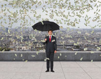Businessman with umbrella and falling dollar Royalty Free Stock Photography
