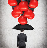 Businessman with umbrella. Hands in boxing red gloves breaking to businessman with umbrella stock photos