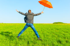 Businessman with umbrella jumping Stock Photography