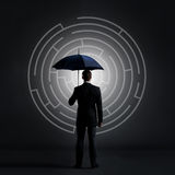 Businessman with an umbrella on a labyrinth. Businessman with umbrella standing over labyrinth background. Business, strategy, insurance, concept Royalty Free Stock Photos