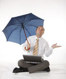 Businessman with umbrella and laptop Stock Photography