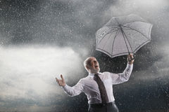 Businessman With Umbrella Laughing In Storm Stock Photo