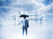Businessman with an umbrella looking at a giant key Stock Photography