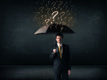 Businessman with umbrella and a lot of drawn question marks Royalty Free Stock Photography