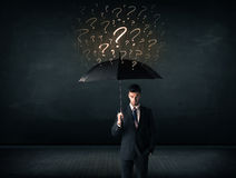 Businessman with umbrella and a lot of drawn question marks Stock Images