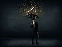 Businessman with umbrella and a lot of drawn question marks Stock Photos