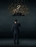 Businessman with umbrella and a lot of drawn question marks Royalty Free Stock Images