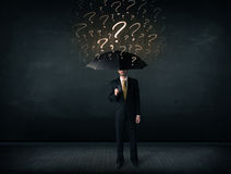 Businessman with umbrella and a lot of drawn question marks Stock Photography