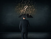 Businessman with umbrella and a lot of drawn question marks Stock Image