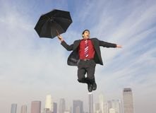 Businessman With An Umbrella In Midair. Full length of an ecstatic businessman with an umbrella in midair Royalty Free Stock Image