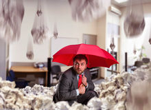 Businessman with umbrella in the office Royalty Free Stock Photos