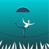 Businessman with an umbrella over the precipice Stock Photo