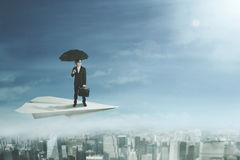 Businessman with umbrella on paper plane Royalty Free Stock Images
