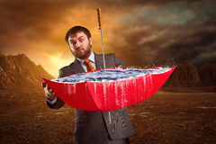 Businessman with an umbrella. Businessman with red umbrella full of water at night Stock Photography
