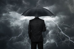 Trouble ahead. Businessman with umbrella standing in front of stormy clouds stock images