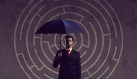 Businessman with umbrella standing over labyrinth background. Bu. Siness, strategy, insurance, concept Stock Photography