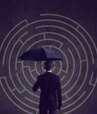 Businessman with umbrella standing over labyrinth background. Bu. Siness, strategy, insurance, concept Royalty Free Stock Images