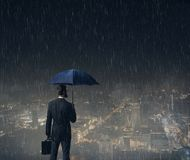 Businessman with umbrella standing over night city background. Business, crisis, failure, concept Royalty Free Stock Photography