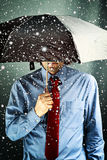 Businessman with umbrella in storm Stock Images
