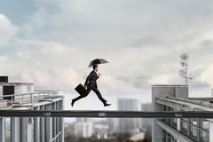 Fearless businessman overcoming difficulty. Mixed media Royalty Free Stock Photography