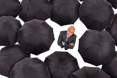 Businessman with umbrellas Stock Images